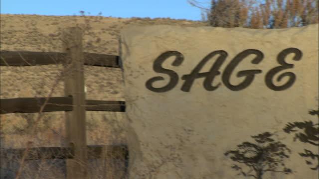 vídeos de stock e filmes b-roll de a decorative stone sign posted to a wooden rail fence identifies sage acres. - vedação