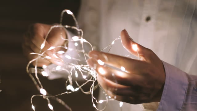 vídeos de stock e filmes b-roll de decorative string lights in hand, untangle. - emaranhado