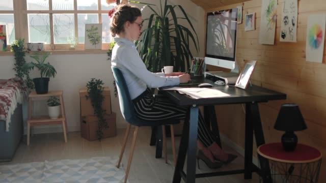 vidéos et rushes de femme d'affaires dédiée travaillant au bureau soigneusement - travailleur indépendant