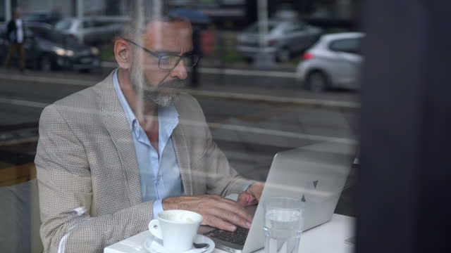 dedicated businessman working at cafe - one mature man only stock videos & royalty-free footage