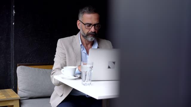 stockvideo's en b-roll-footage met toegewijde zakenman die bij koffie werkt - driekwartlengte