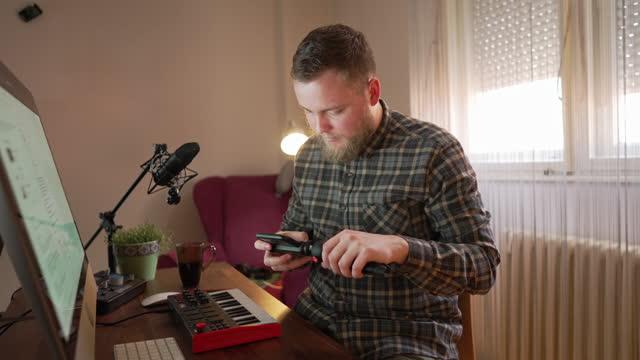 vídeos de stock, filmes e b-roll de músico masculino dedicado, preparando seu celular e tripé, antes de começar com seu vlog, para conversar com seu público sobre que equipamento você precisa para fazer música para iniciantes - preparação