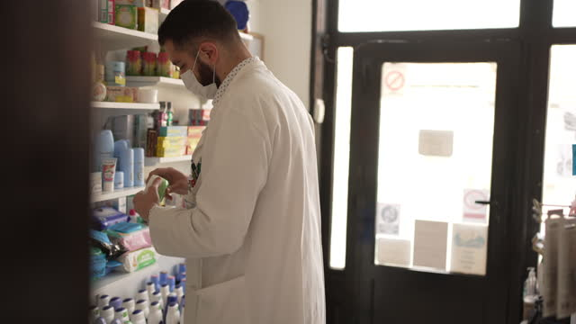 dedicated male pharmacist checking the expiration date on products in his drugstore - sales occupation stock videos & royalty-free footage