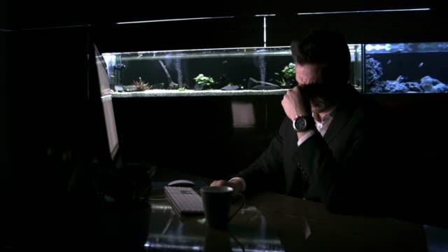 vídeos de stock e filmes b-roll de dedicated, tired businessman working late at computer in office with fish tank, real time - aquário edifício para cativeiro animal
