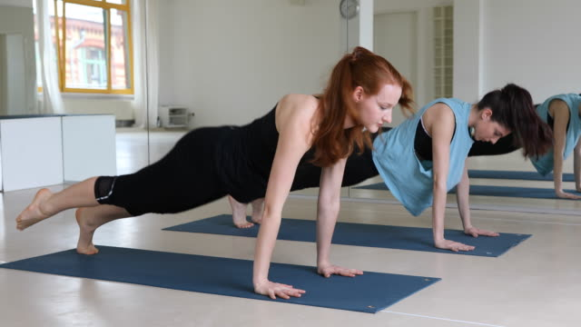 Dedicated women exercising yoga at health club