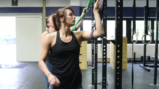 dedicated women pulling resistance bands in gym - pampering self stock videos and b-roll footage