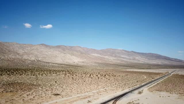 vídeos y material grabado en eventos de stock de cielo azul intenso sobre tren pistas en desierto de california - oasis desierto