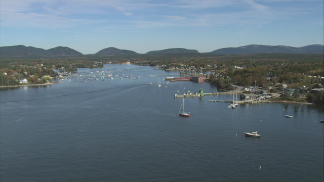 aerial deep cove with docks and anchored boats, hills beyond, commercial buildings and village nestling in woodland with autumn colors / bass harbor, maine, united states - anchored stock videos & royalty-free footage