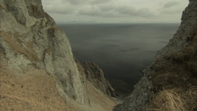 vidéos et rushes de a deep crevice between two rocky ridges reveals a gray sea. - géologie
