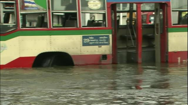 Deep flood water surrounds a Bangkok bus