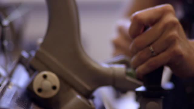 Deep focus Shot of a Woman Using a Knitting Machine