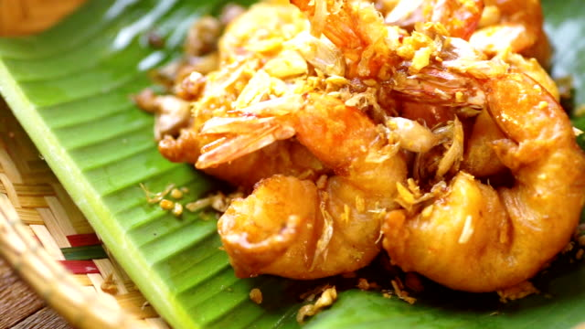 Deep fried shrimp with garlic and pepper served on banana leaf in basket, Thai cuisine.