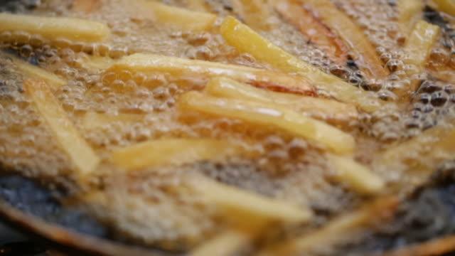 vídeos de stock, filmes e b-roll de deep frying potatoes - espátula