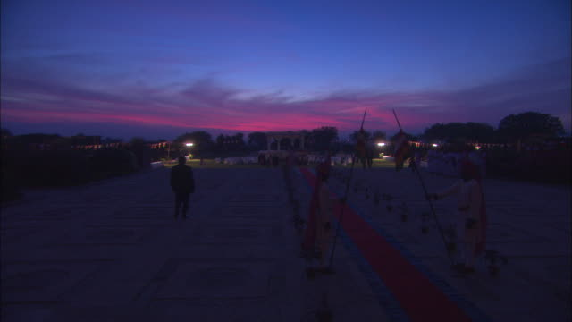 vídeos de stock, filmes e b-roll de deep red sun sets behind social gathering at jaipur palace. available in hd. - pouca luz