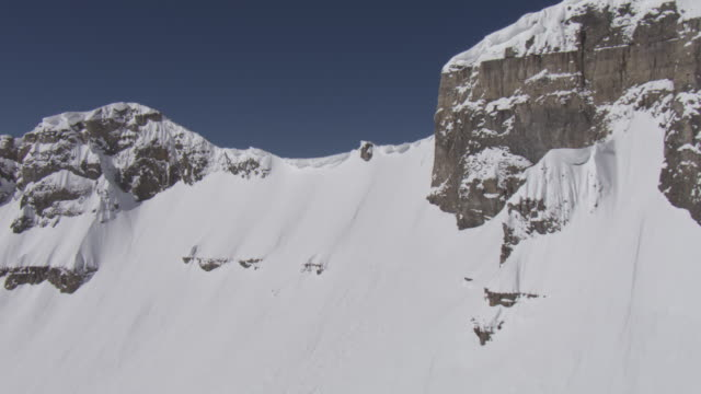Deep snow buries rugged cliffs and slopes in the Wasatch Mountains, Utah.