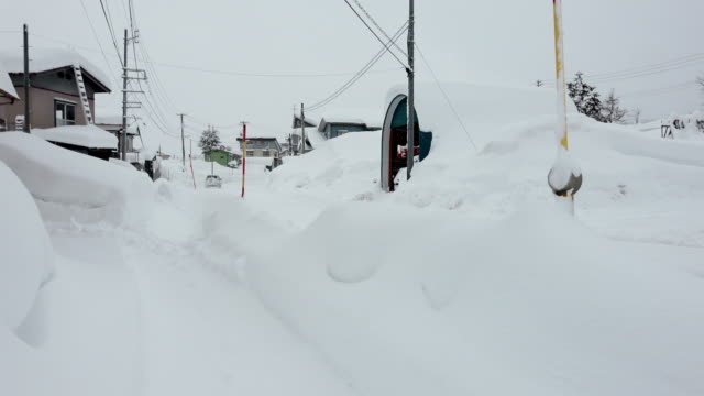 deep snow drifts bury town after major winter storm hits japan - 深い雪点の映像素材/bロール