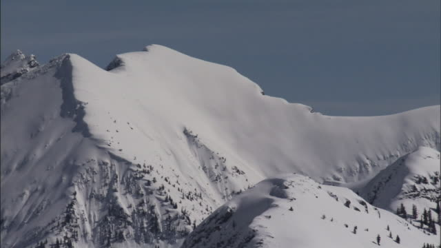 deep snow lies on a slope beneath a mountaintop. - hill stock videos & royalty-free footage