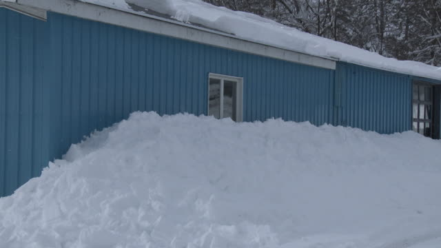 deep snow piled up against the side of a building - schneebedeckt stock-videos und b-roll-filmmaterial