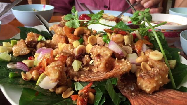 deep-fried sea bass with spicy mixed herb salad - sea bass stock videos & royalty-free footage