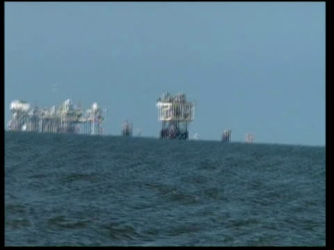 deepwater horizon rig seen in distance and reporter looking at rig from deck of boat / professor rick steiner pointing out oil slick on water and... - gulf of mexico stock videos & royalty-free footage