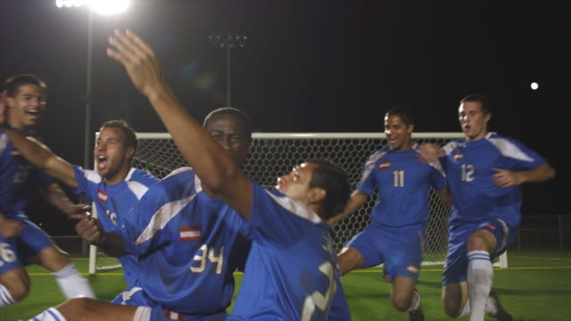 A soccer team celebrates victory on the field.