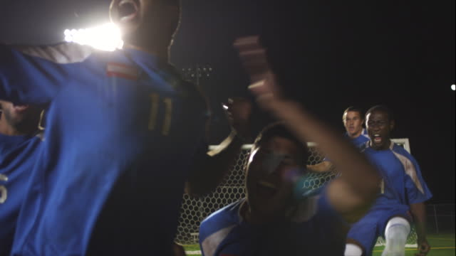 slo mo. defeated soccer goalie crouches down inside a soccer net while the winning team celebrates their victory on the field during a nighttime match - football team stock videos & royalty-free footage