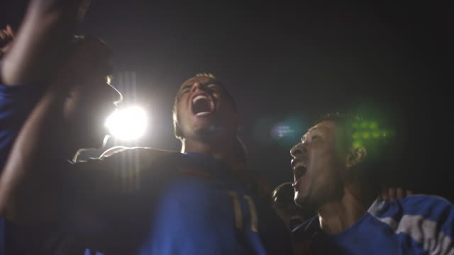 vídeos de stock e filmes b-roll de slo mo. defeated soccer goalie crouches down inside a soccer net while the winning team celebrates their victory on the field during a nighttime match - ecstatic