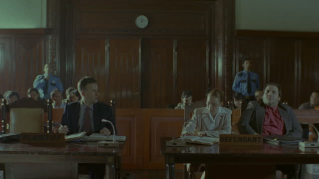 defendant and defending counsel next to the prosecutor inside a courtroom during a legal trial. - 裁判点の映像素材/bロール