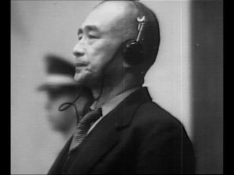stockvideo's en b-roll-footage met defendants in dock at tokyo war crimes tribunal / japanese admiral shigetaro shimada sits in dock, wearing translation headphones; mp stands behind... - mp