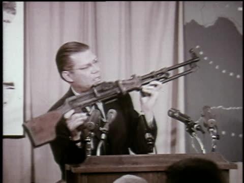 Defense Secretary Robert McNamara holds up Chinese machine gun during press conference