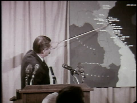 Defense Secretary Robert McNamara points at map during press conference