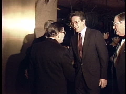 defense secretary-designate john tower enters a room with companion dorothy heyser and shakes hands with men. - 米国国防総省点の映像素材/bロール