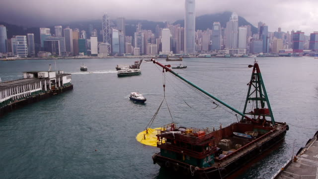 deflated rubber duck in hong kong with crane boat - wide shot - spoonfilm stock-videos und b-roll-filmmaterial