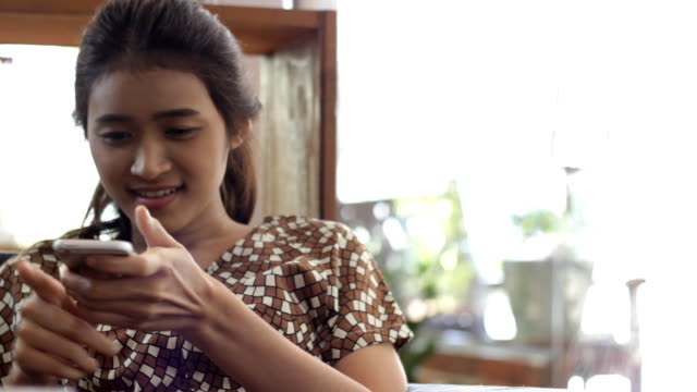 defocus: girl with smartphone in the cafe smile face - hot desking stock videos & royalty-free footage