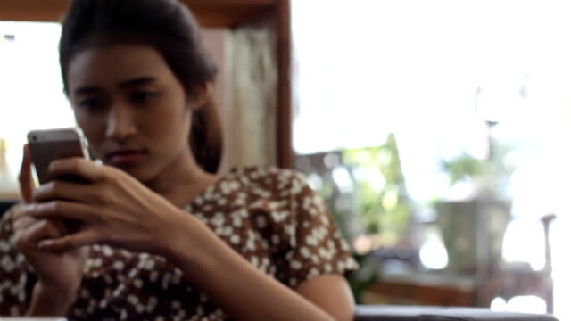 defocus: girl with smartphone in the cafe - hot desking stock videos & royalty-free footage