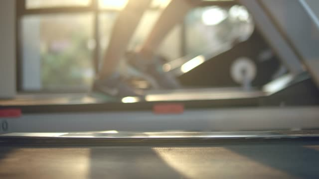defocus : young woman working out and jogging on treadmill at gym - health club stock videos & royalty-free footage