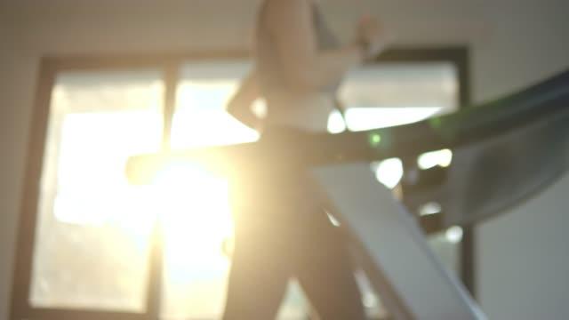 defocus: junge frau trainieren sich und joggen auf laufband im fitnessstudio - trainingsraum wohnraum stock-videos und b-roll-filmmaterial