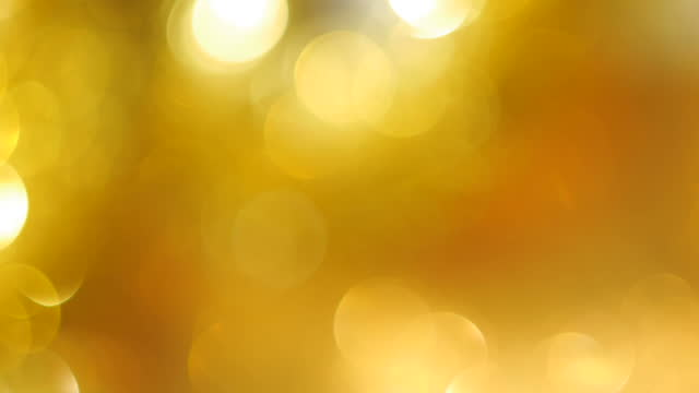 defocused bright gold colored blinking lights creating soft bokeh circles as background - bright colour stock videos & royalty-free footage