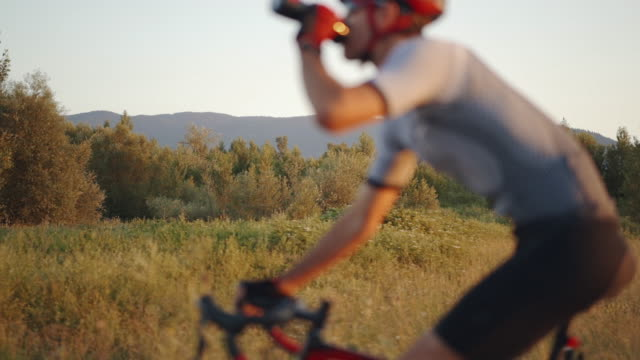 vídeos de stock e filmes b-roll de defocused close up footage of male triathlete feet cycling a bicycle in the evening, in a sunny day. road bike detailed close up shot during sunset focus on background - bicicleta de corrida
