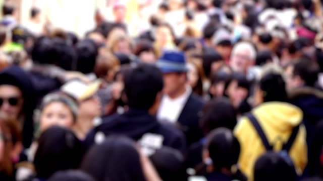 defocused crowd of people walking in a busy street in tokyo - abundance stock videos & royalty-free footage