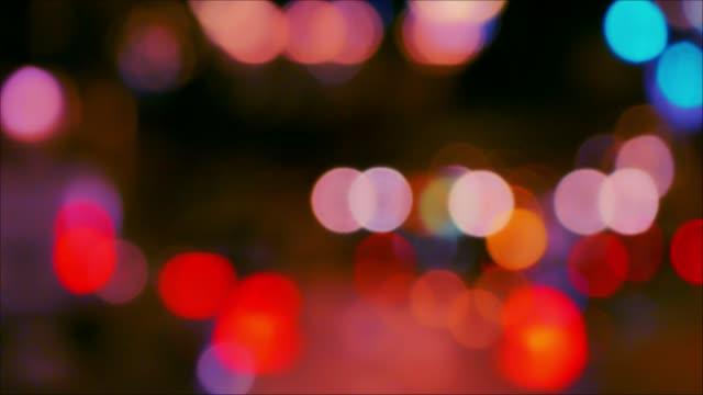 ヘッドライトとテールランプ、夜の街では車のデフォーカス - テールランプ点の映像素材/bロール