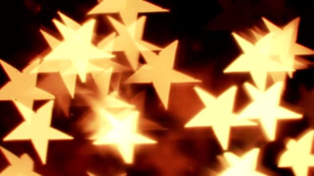vidéos et rushes de reflets lumineux défocalisés en forme d'étoiles. bouclables fond - image détériorée