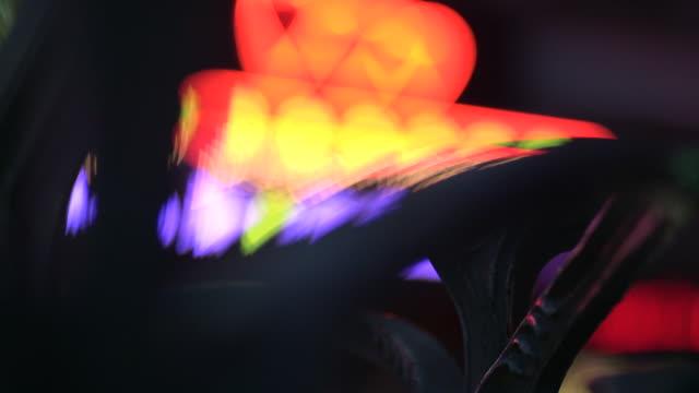 vidéos et rushes de defocused lights in the red light district of pigalle flash behind art-deco ironwork, paris, france. - lumière disco
