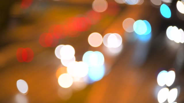 defocused lights street abstract . city blur background. moving bokeh circles of night traffic. - selective focus stock videos & royalty-free footage