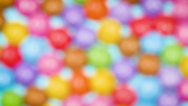 vídeos de stock e filmes b-roll de defocused overhead view of colourful chocolate sweets slowly revolving - combinação química