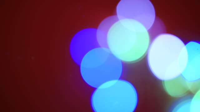 stockvideo's en b-roll-footage met defocused panning shot across blue, green and white fairy lights. - stippen