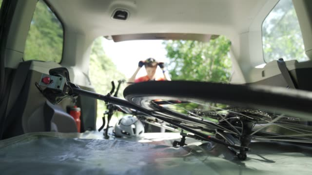vídeos de stock e filmes b-roll de defocused professional cyclist taking down her bicycle from the car trunk ready to cycle - triatleta