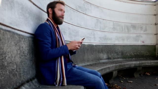 defokussierten szene eines geschäftsmannes verwendet smartphone - lässige kleidung stock-videos und b-roll-filmmaterial