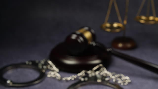 defocused shot gavel, handcuffs and justice scale - small group of objects stock videos & royalty-free footage