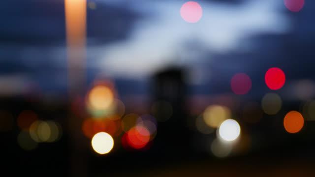 defocused shot of multi-coloured lights at night - デフォーカス点の映像素材/bロール